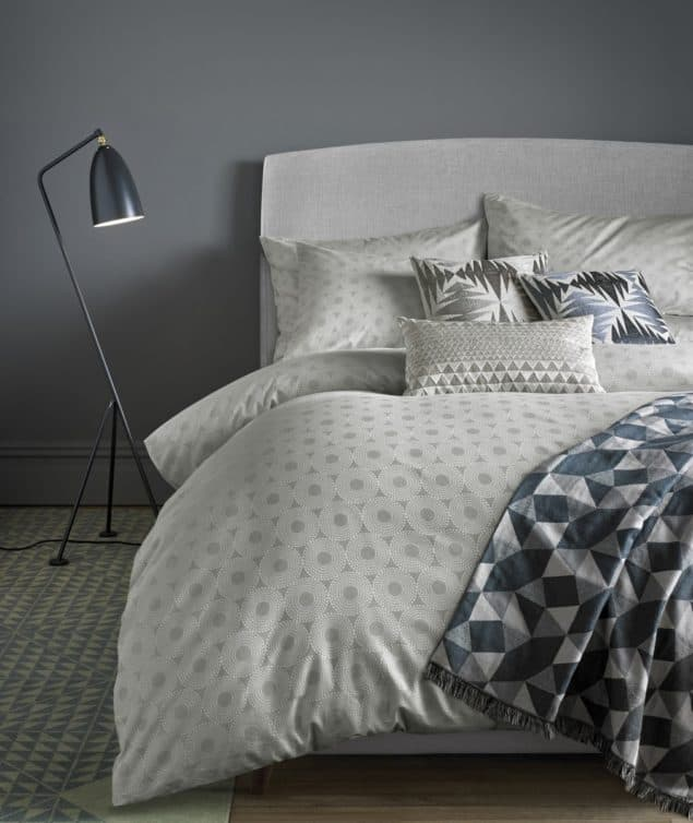 Contemporary bedroom featuring a cosy bed made up with silver geometric bedding from Niki Jones