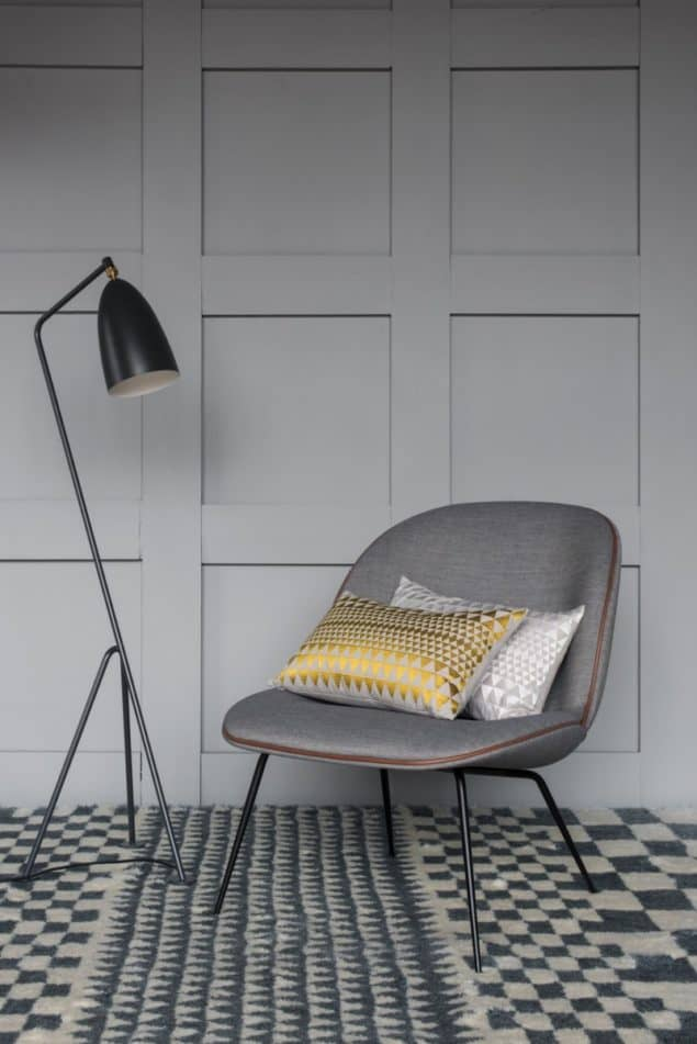 Chair and floor lamp placed on a grey geometric rug by Niki Jones