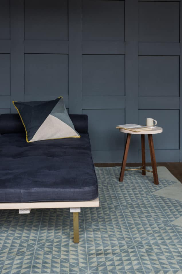 Grey room featuring a geometric rug and cushion by Niki Jones