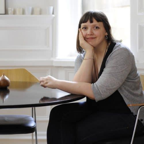 Interior Designer Niki Jones sat at a desk smiling