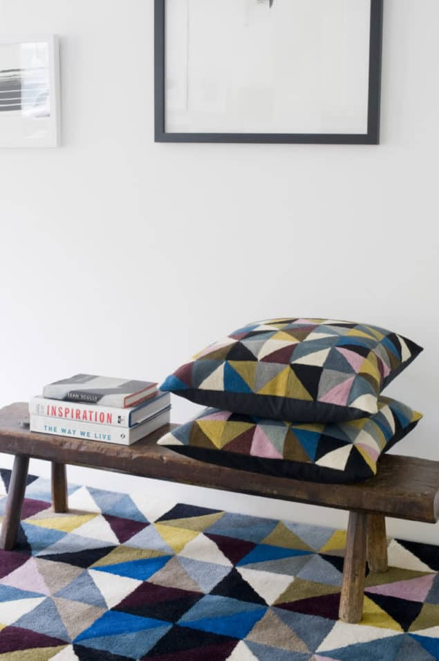 Geometric cushions placed upon a bench which rests on a geometric rug by Niki Jones
