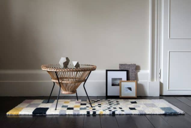 Coffee table placed on a geometric rug by Niki Jones
