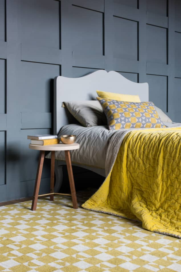Grey bedroom featuring a yellow geometric rug and bedding from Niki Jones