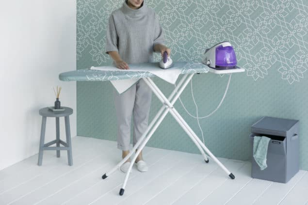 Lady ironing using a solid steam unit and a Brabantia Ironing Board