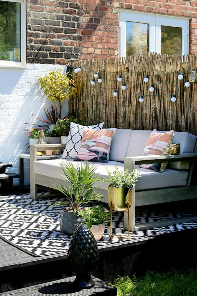 Swoonworthy Garden Makeover featuring reed screening, outdoor sofa and outdoor rug