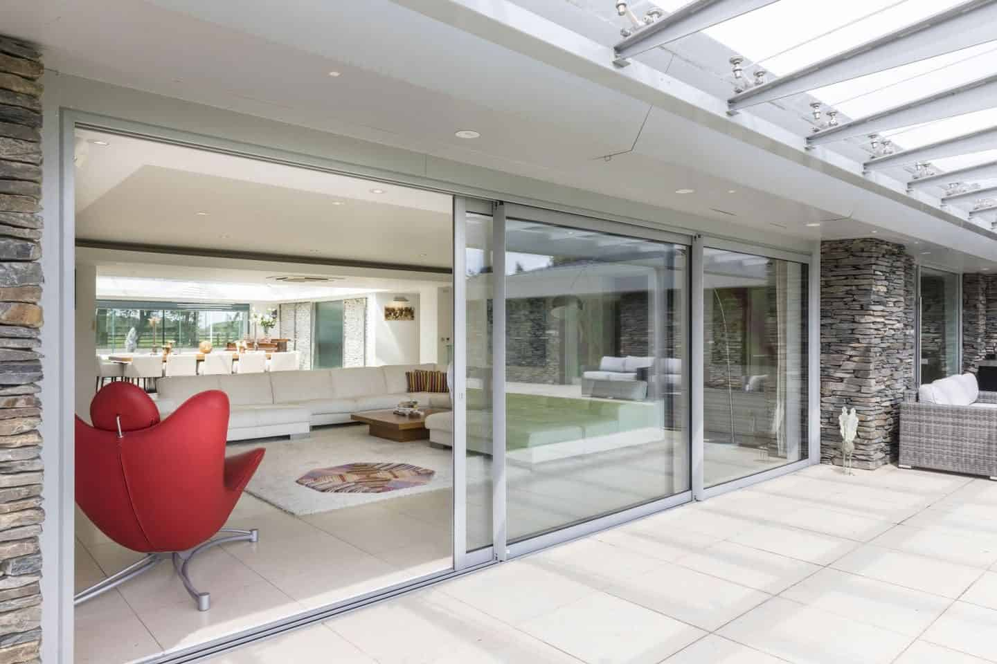 Pilkington Glass large glazed sliding doors from living room leading out onto a garden patio