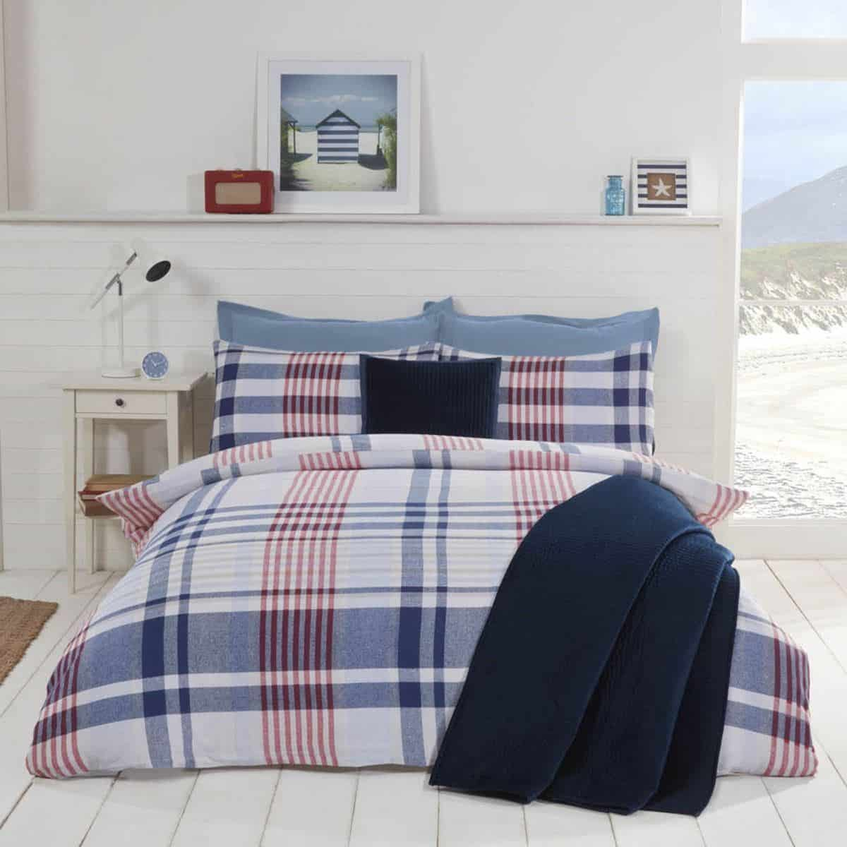 A blue and white nautical themed bedroom featuring checked bedding. Blue is a very calming colour and great for helping to achieve good quality sleep.
