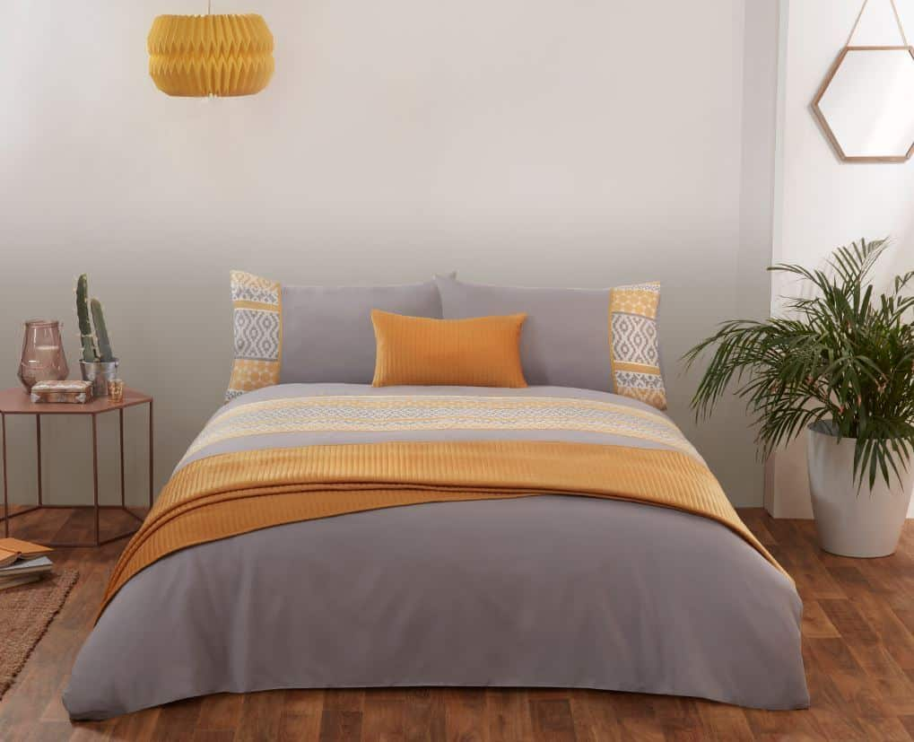 A grey and ochre bedroom with wooden flooring and plants