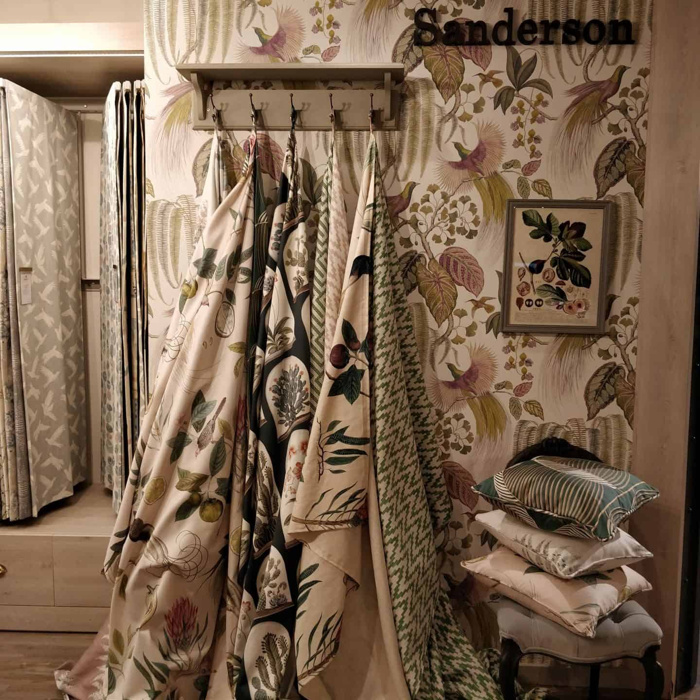 A display of fabrics and cushions and wallpaper by Sanderson
