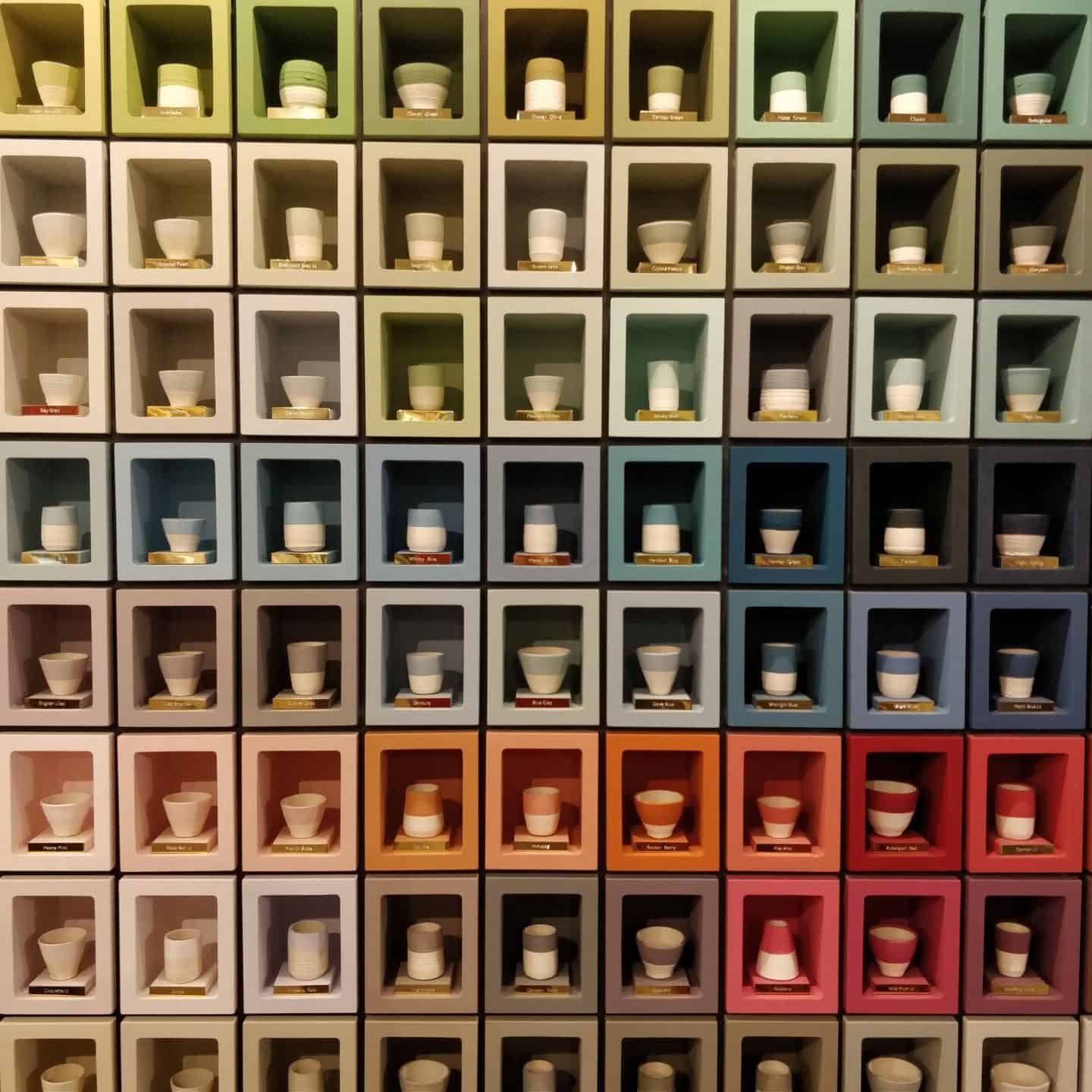 A selection of paint colours displayed in small cubes containing painted pots.