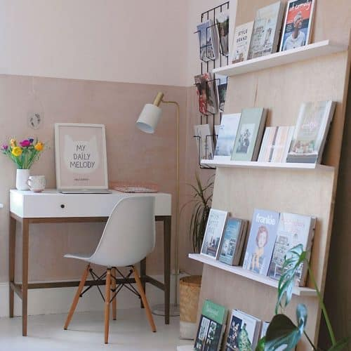 A small office space in the corner of a room uses leaning shelves to avoid damaging the wall