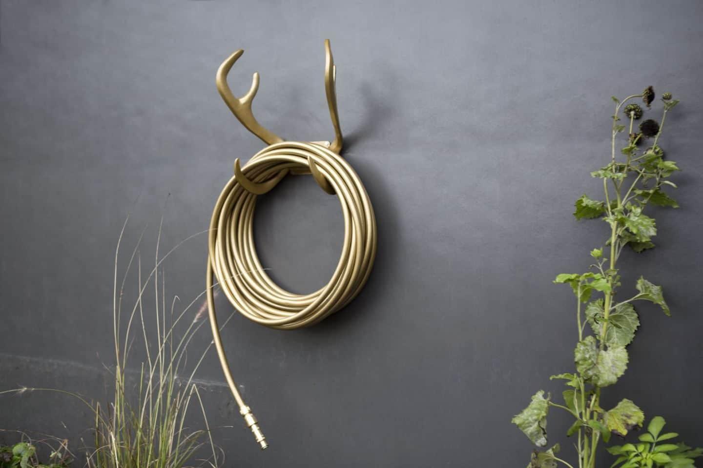 Garden Glory - Stylish garden equipment - gold garden hose wall-mounted on gold antlers