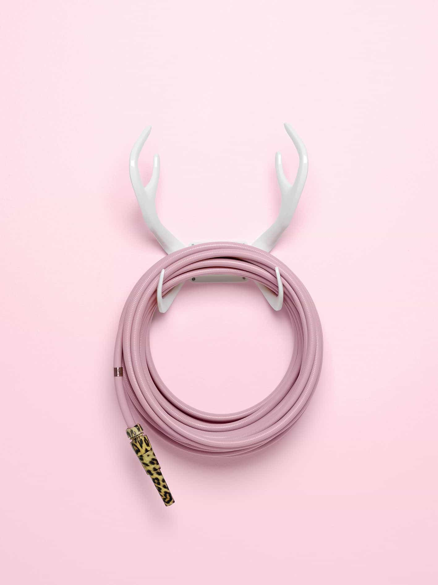 Garden Glory - Stylish garden equipment - pink garden hose with leopard print nozzle wall-mounted on white antlers
