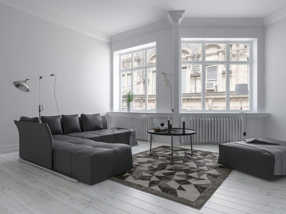 Radiator buying guide featuring column radiators below the windows in a monochrome living room