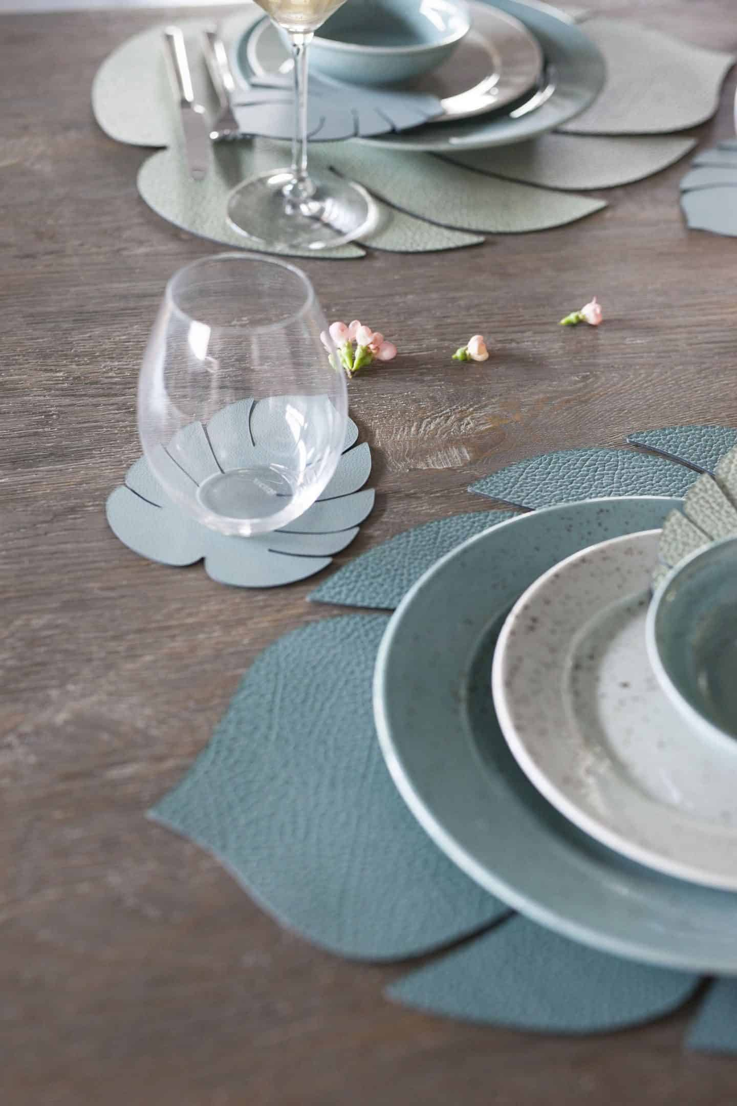 Green recycled leather placemats in th eshape of monstera leaves by LIND DNA