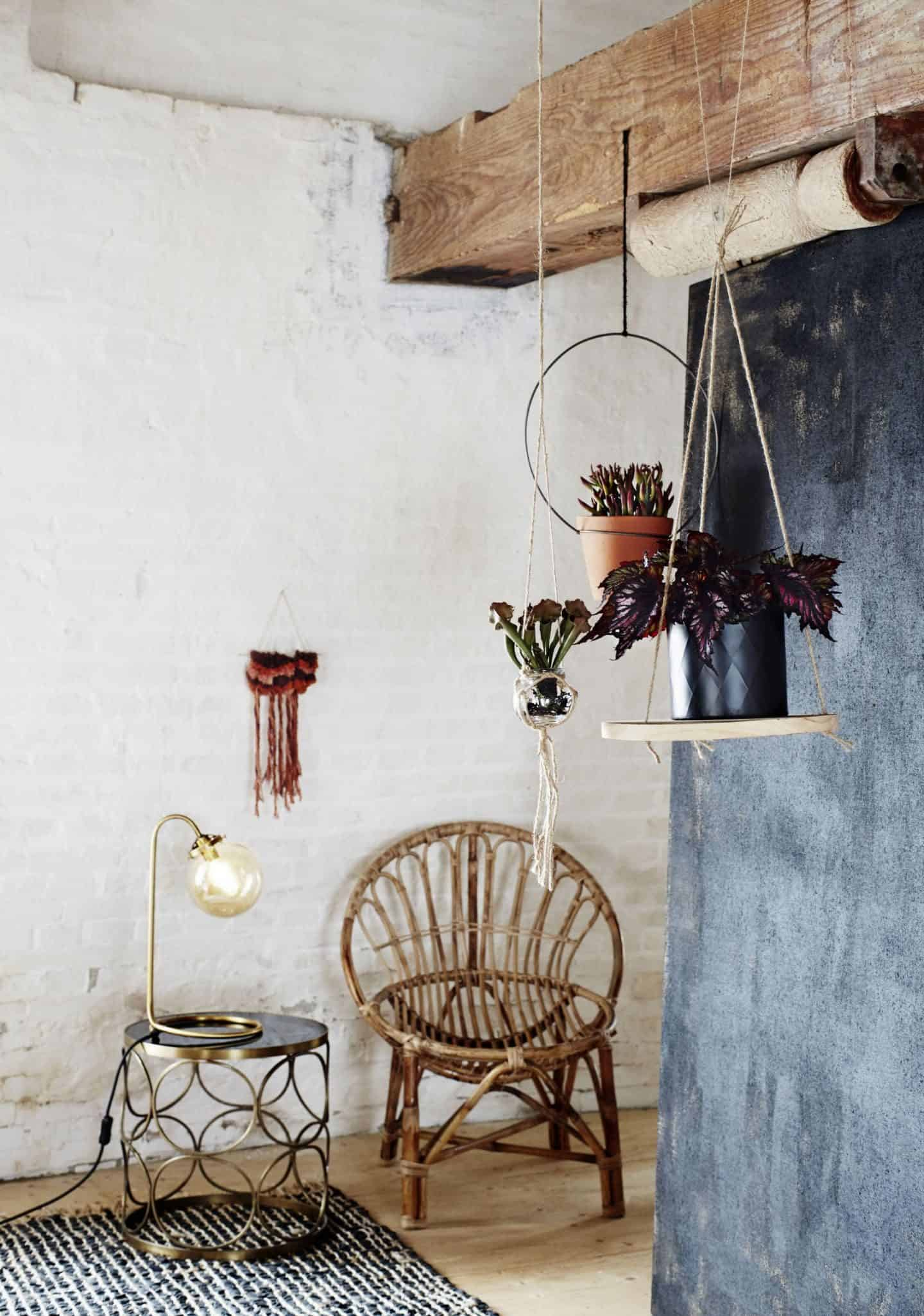 A bohemian style display from Madam Stolz featuring bamboo furniture and plants hanging from the rafters of a rustic style room