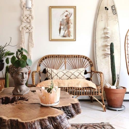 A bohemian style lounge featuring lots of natural materials, macrame wall hanging, terracotta pots and a surf board