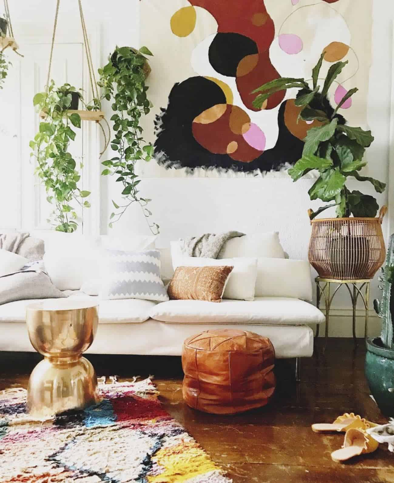 A bohemian style lounge featuring wall hangings, plants, leather Moroccan pouffes in earthy colours
