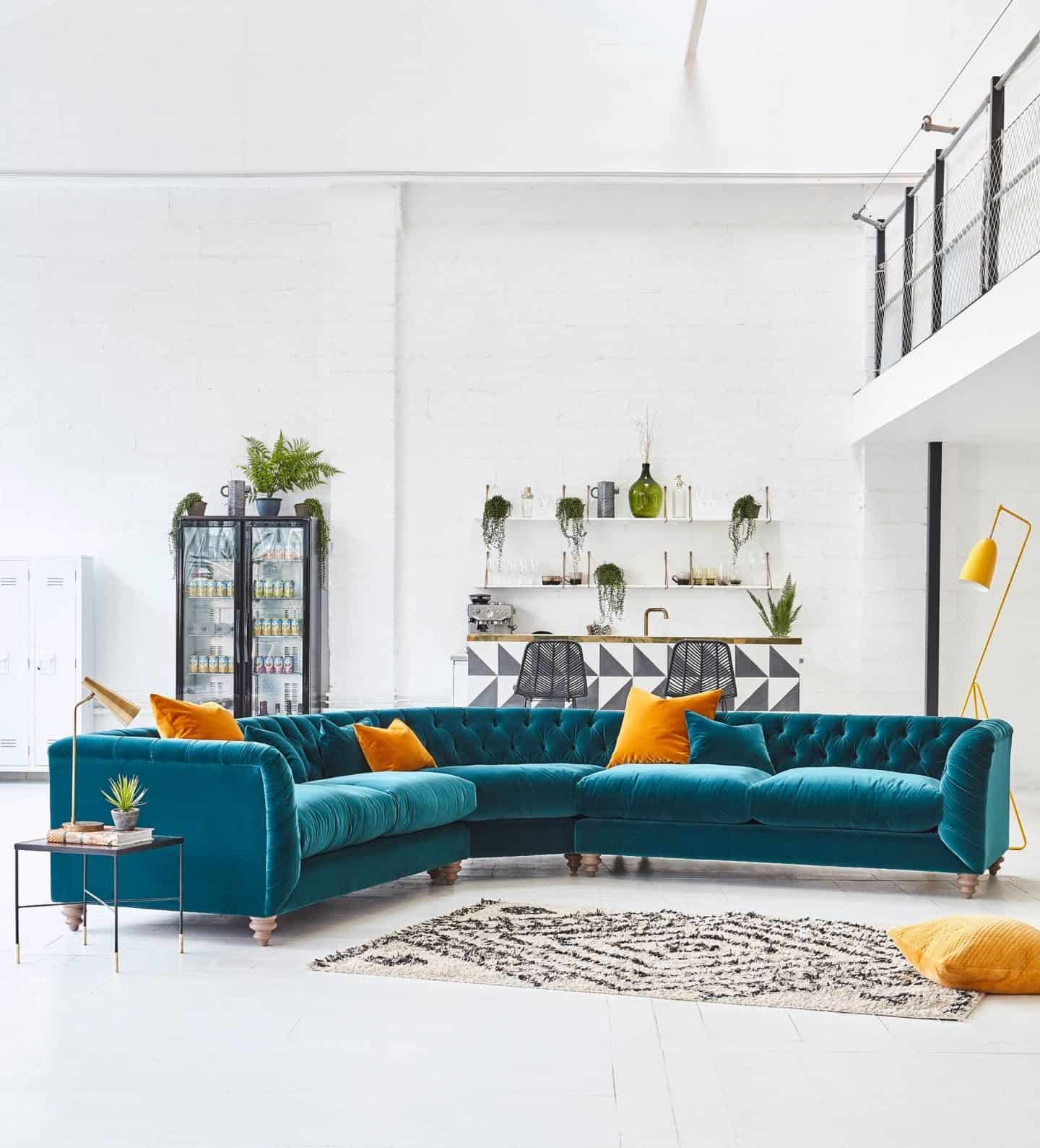 A large turquoise velvet corner sofa  from Darlings of Chelsea with mustard yellow scatter  cushions sits in a warehouse setting. Furniture can be found on furniture comparison website Kuldea