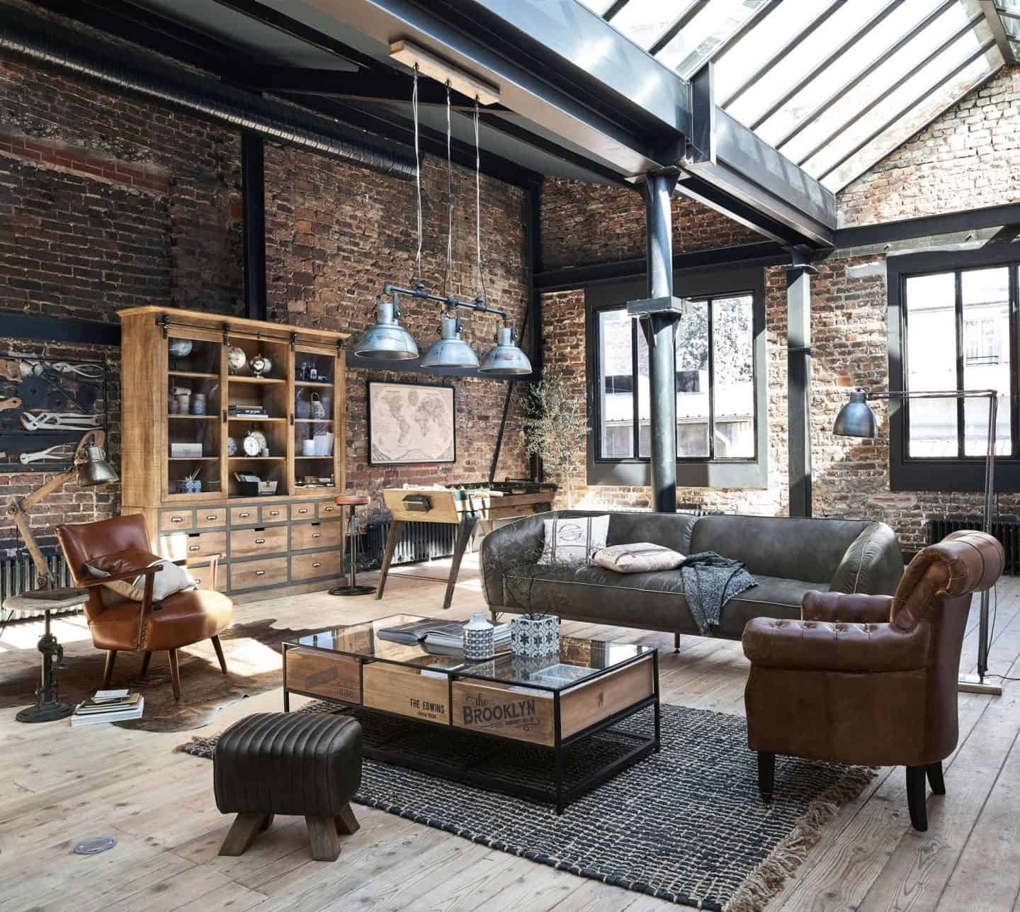 An industrial style living room featuring exposed brick walls, steel beams and industrial style lighting.