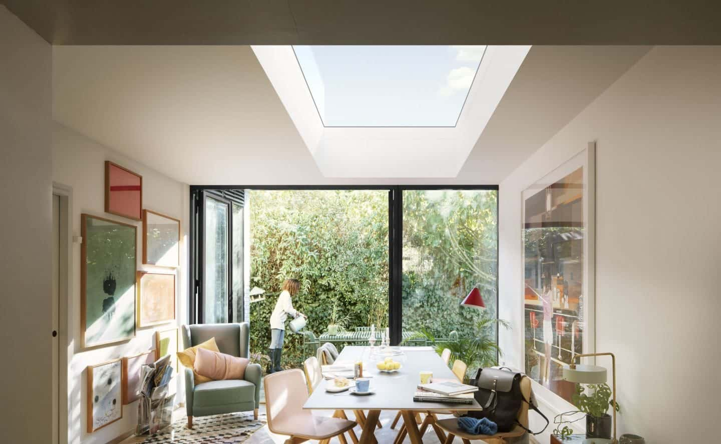 Vario by VELUX Bespoke Flat Roof Windows pictured above a dining room. Women seen outside bi-fold doors watering the garden.