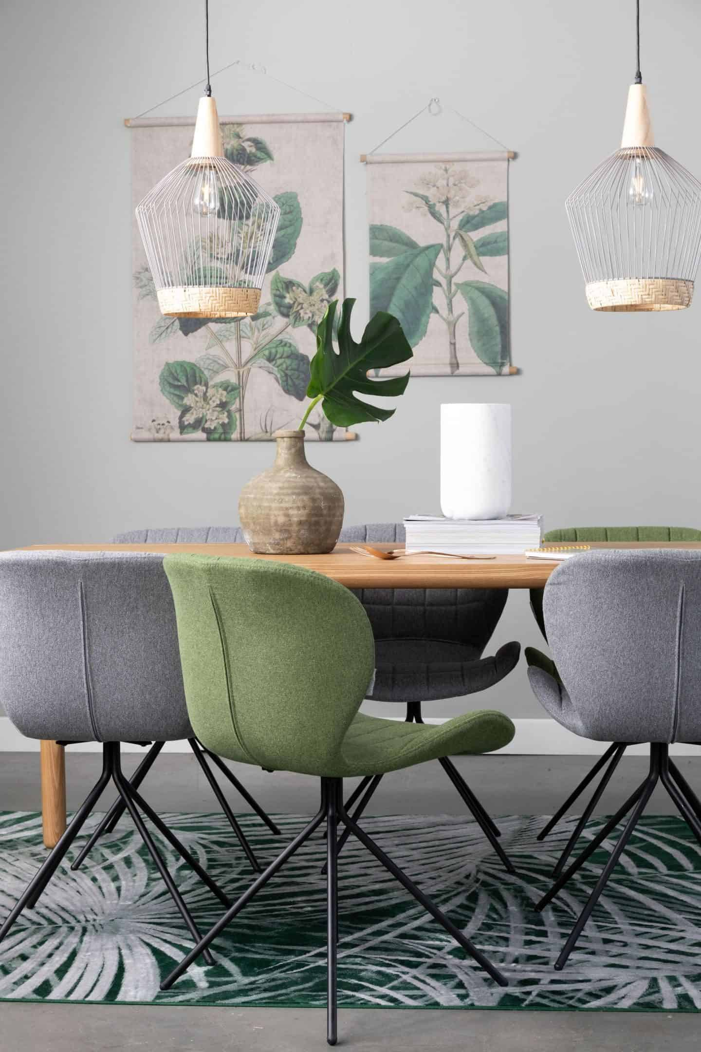 A desk or dining table with chairs around and two pendant lights suspended above. Botanical prints hang on the wall behind.