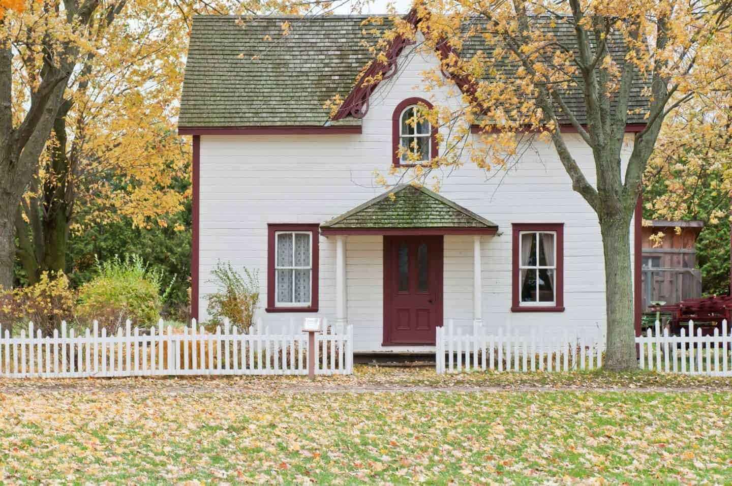 A beautiful detatched home in the atumn with orange leaves falling from the trees and scattered on the floor.