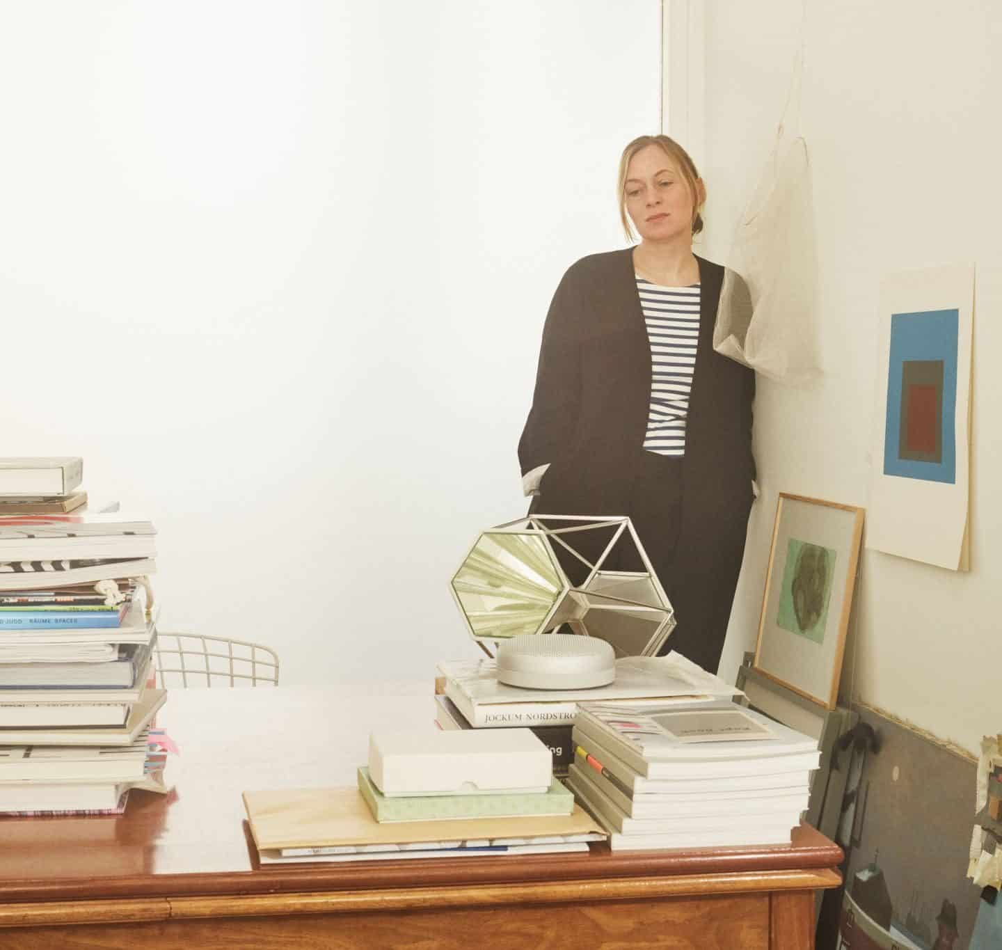 Danish designer Cecilie Manz standing behind a desk piled high with books.