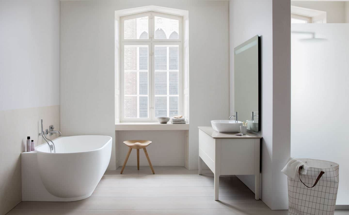 The Luv sanitary ware collection by luxury bathroom brand Duravit. A bathtub stand opposite a sink with a window behind.