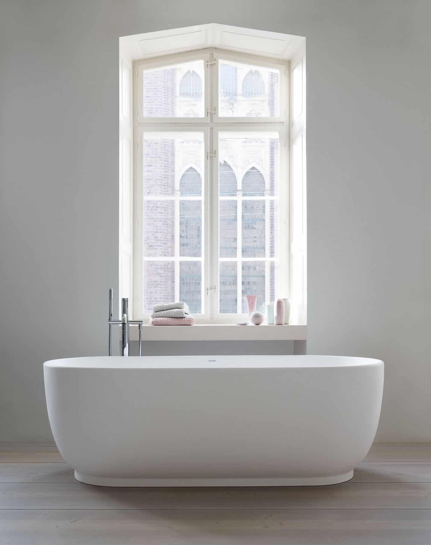 A freestanding bathtub infront of a large window. Bathtub from the Luv collection by luxury bathroom brand Duravit.