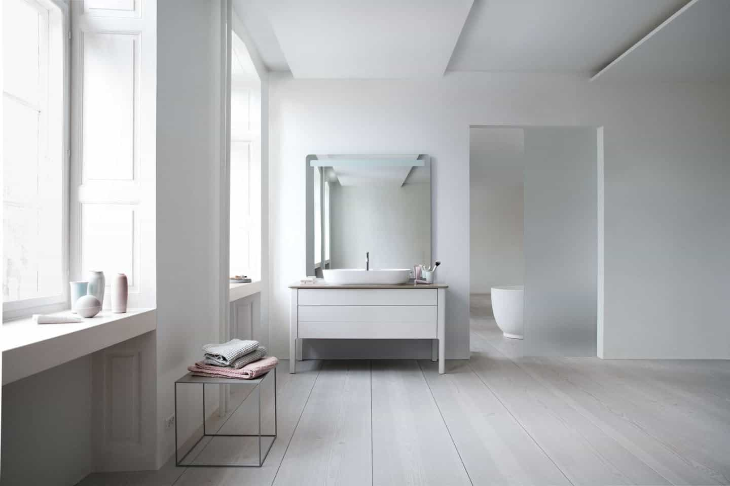 The Luv collection by luxury bathroom brand Duravit. Two large windows on the left and a basin on the adjacent wall.
