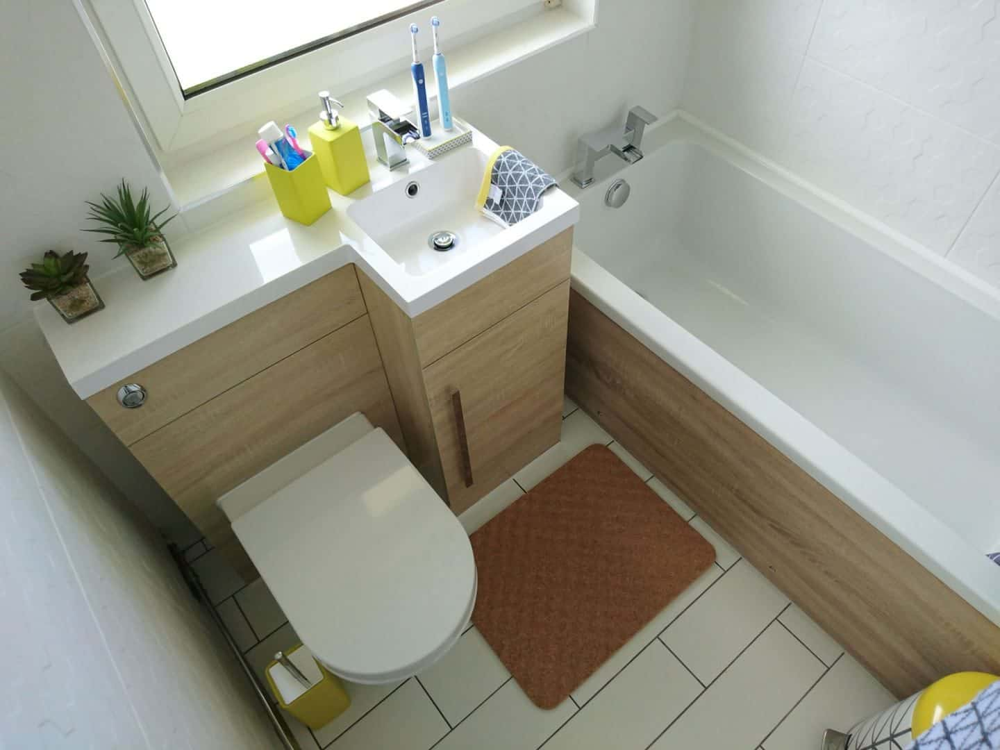 A small bathroom with white tiles and floor, natural wood and pops of yellow