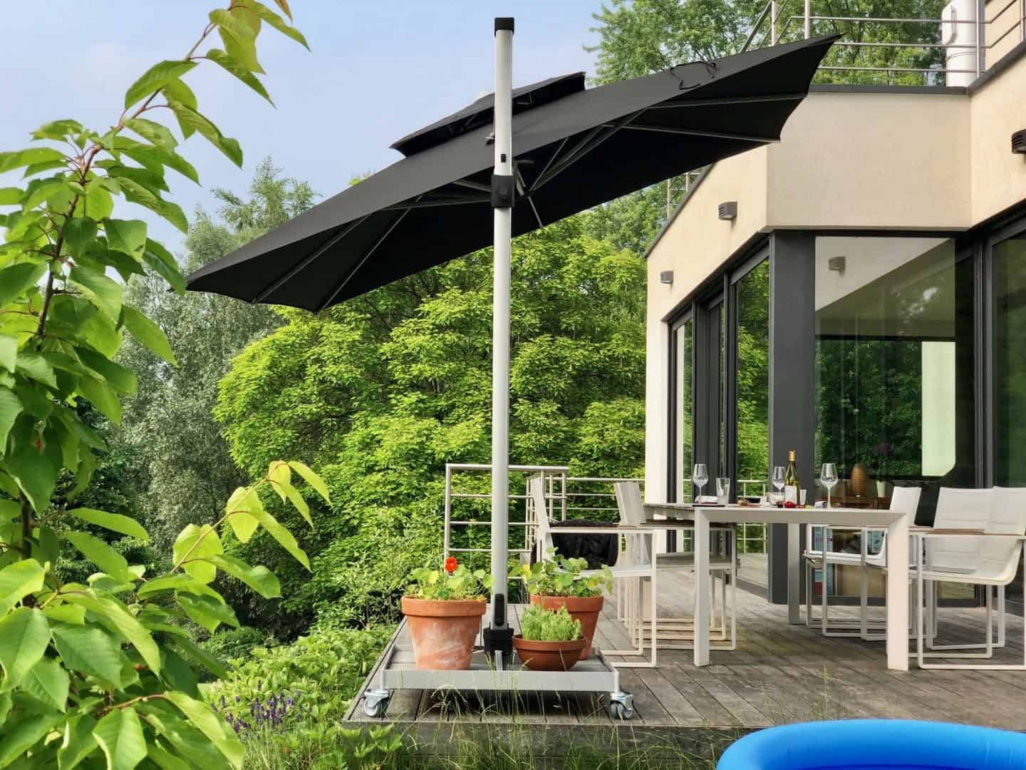 Garden Parasol from Solero Parasols. Large square garden parasol on a wheeled base. The parasol is angled over the garden furniture.