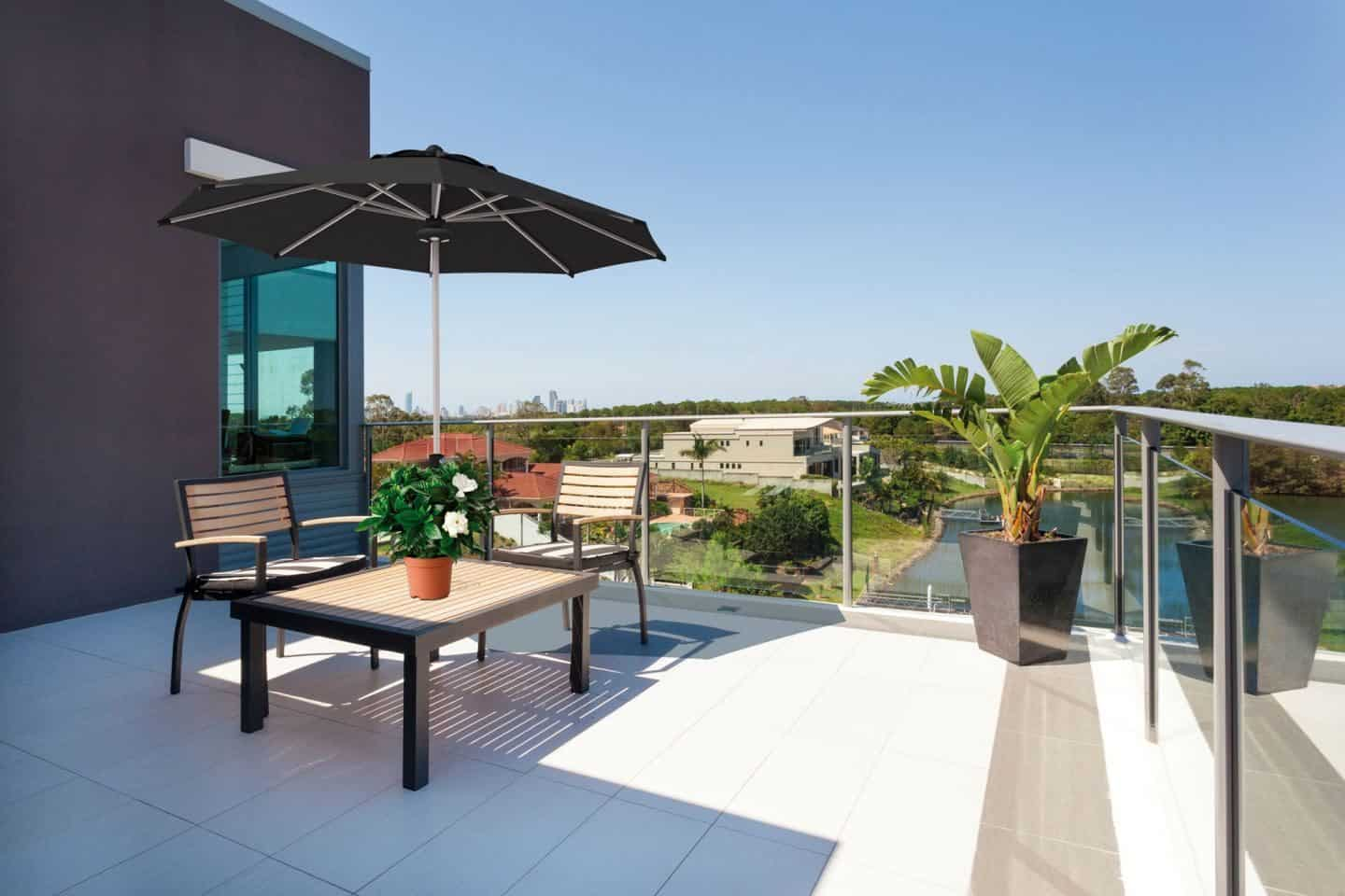 Garden Parasol from Solero Parasols.  Large black garden parasol above an outdoor furniture set on a terrace.