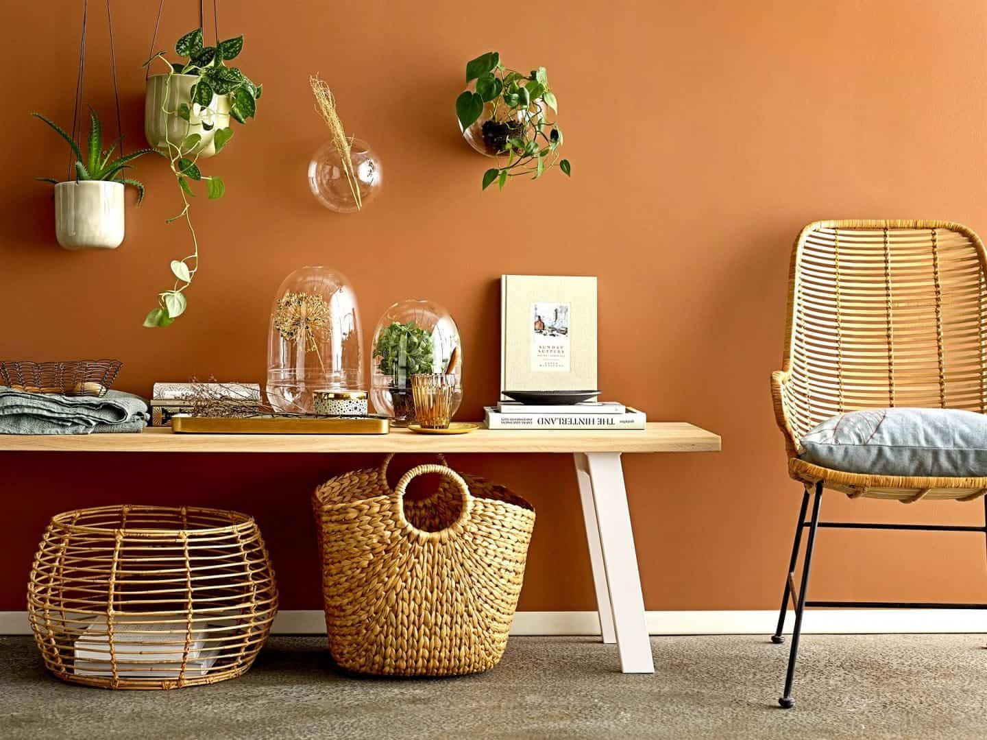 Shekåbba The Danish Home stocks a range of Danish homewares. A coffee table, baskets and rattan chair against a terracotta wall dotted with hanging plants