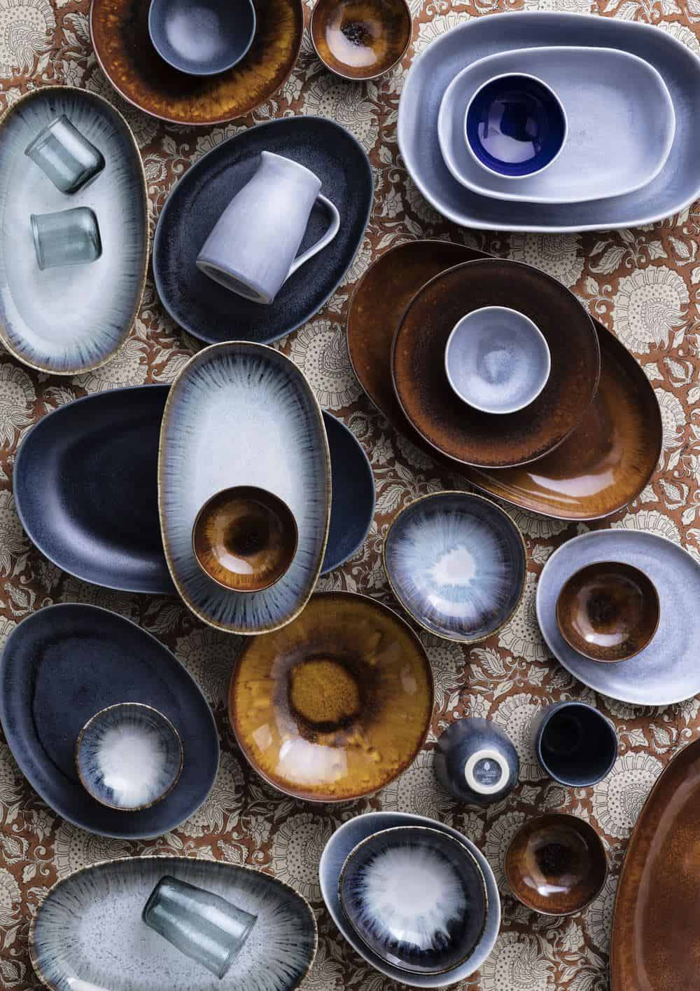 Shekåbba The Danish Home stocks a range of Danish homewares. A table seen from above full of ceramic serveware in earthy tones