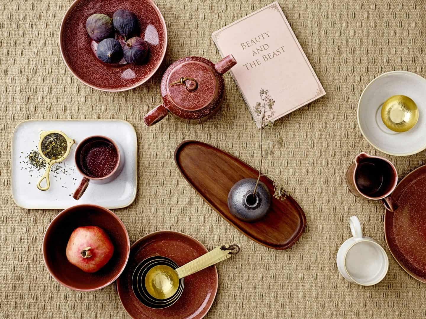 Shekåbba The Danish Home is an online retailer that stocks a range of Danish homewares. Flatlay of rustic ceramics on a textured tablecloth