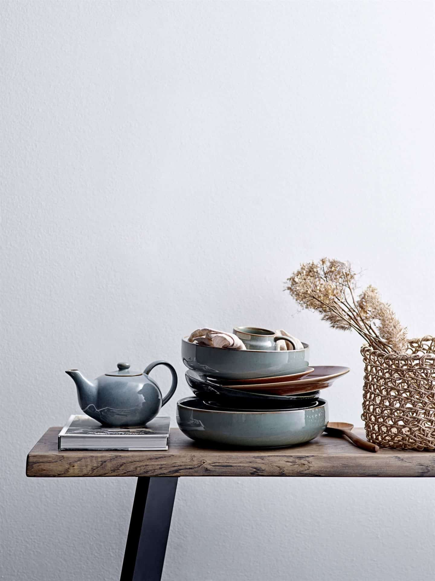 Shekåbba The Danish Home stocks a range of Danish homewares. A table stacked high with blue ceramic plates and a tea pot