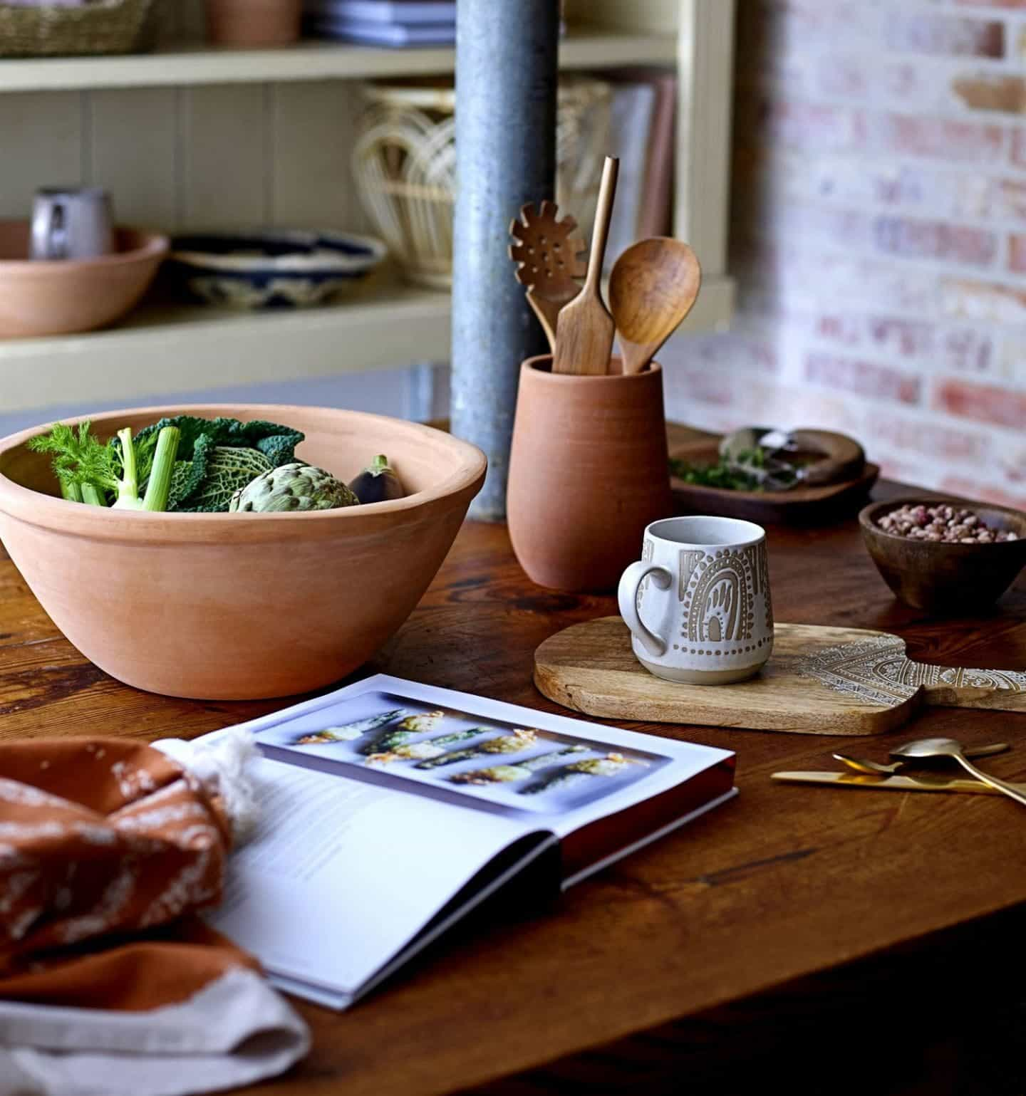 Shekåbba The Danish Home stocks a range of Danish homewares. An earthenware bowl of vegetables on a wooden tabletop next to a pot of wooden utensils a mug of tea and a cookbook.