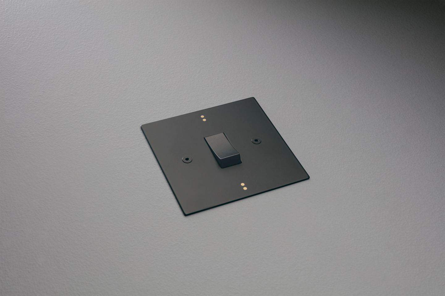 Designer light switches by Kelly Hoppen for Focus SB. Dot is a black light switch featuring two small metallic dots at the top and bottom of the plate.