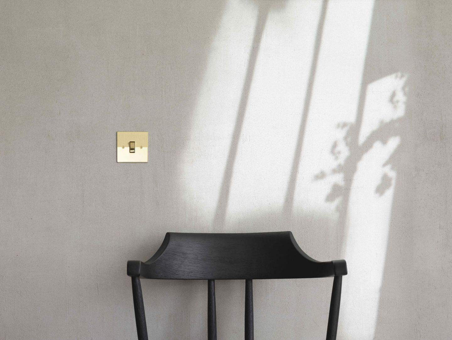 Designer switches and sockets by Kelly Hoppen for Focus SB. A gold light switch on a grey wall above a black wooden chair.