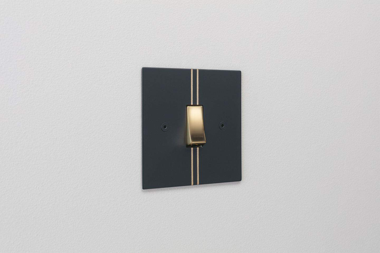 Designer light switches by Kelly Hoppen for Focus SB. Pinstripe is a matt black switch plate featuring two metallic gold pinstripes and a gold switch.
