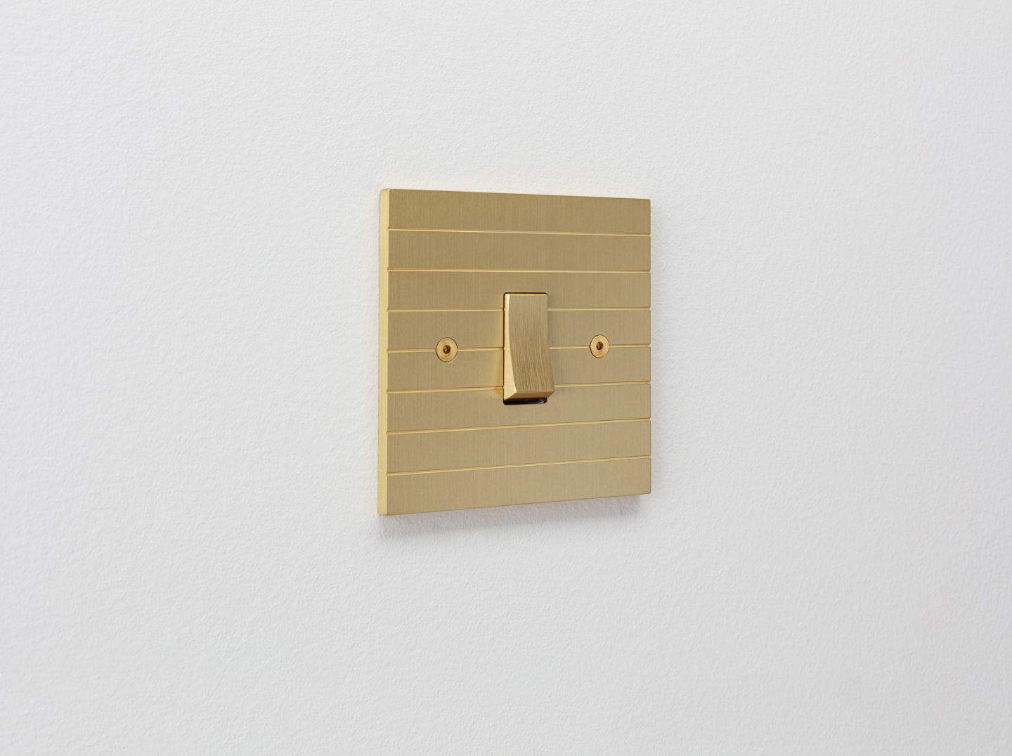 Designer light switches by Kelly Hoppen for Focus SB. Plank is a gold light switch inspired by planks of wood and featuring horizontal grooves.