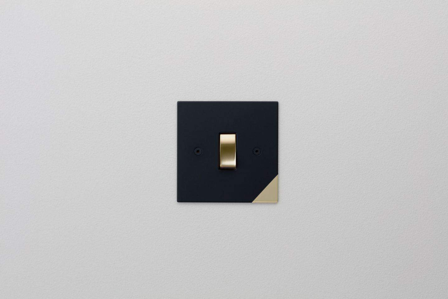 Designer light switches by Kelly Hoppen for Focus SB. Corner is a matt black switch plate with a gold switch and a subtle gold triangle in the bottom right-hand corner.
