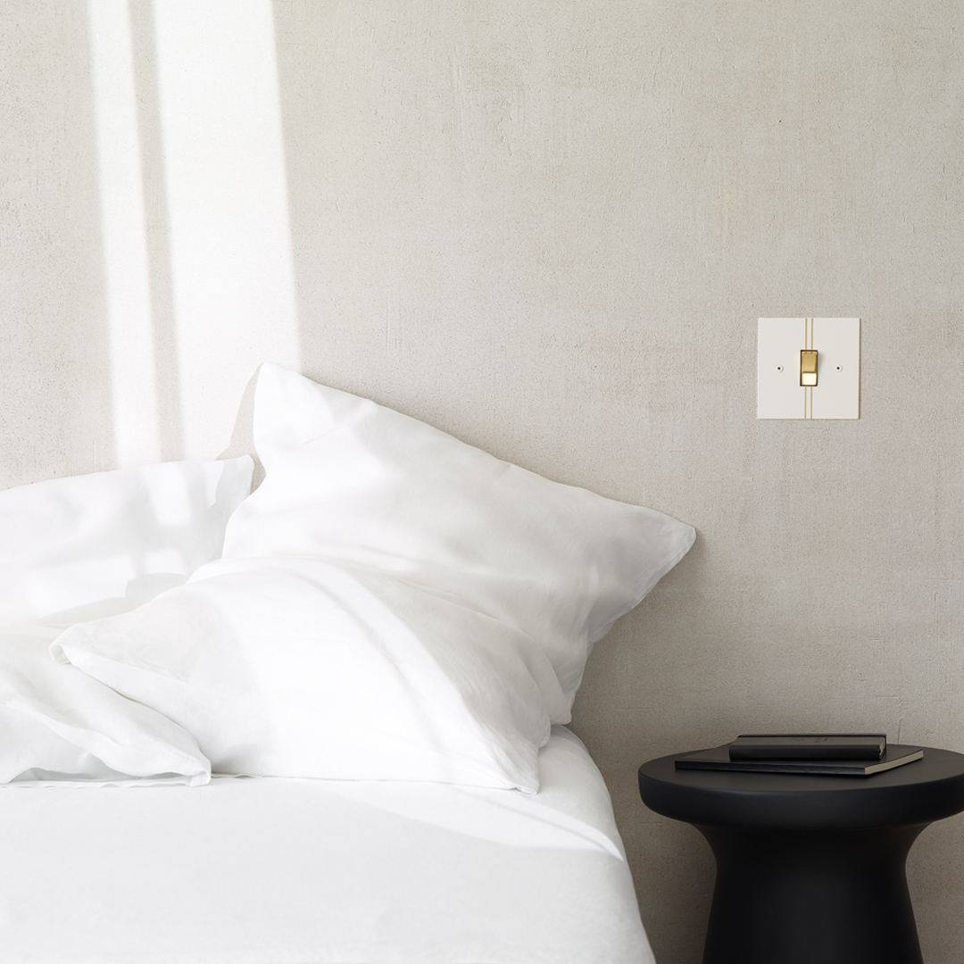 Designer light switches by Kelly Hoppen for Focus SB. A white light switch on a grey wall beside a bed made up with crisp white bed linen.