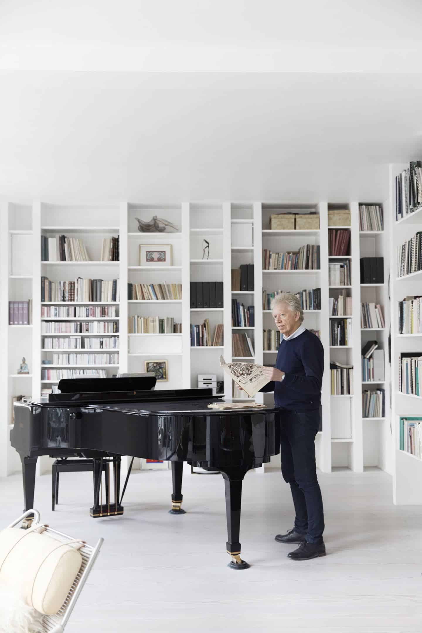Mogens Dahl, husband of Vipp Owner Jette Egelund stood at a concert piano in their converted factory home