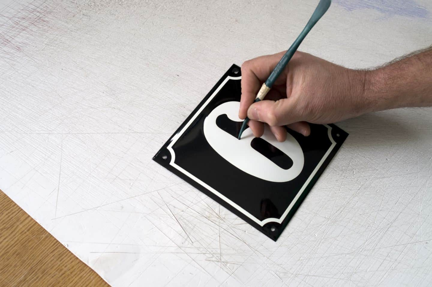 Hand-painting enamel signs for homes and businesses at Ramsign