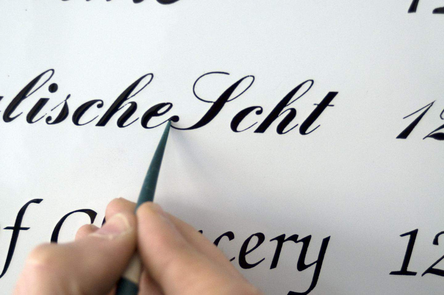 Hand-painting enamel signs for homes and businesses