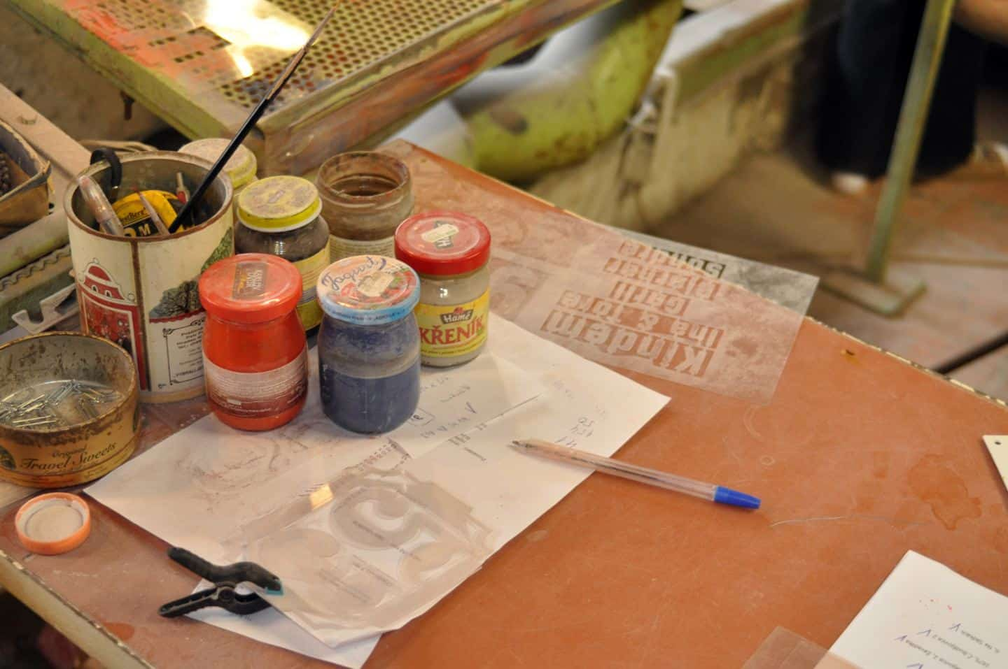 Production of enamel signs for homes and businesses by Ramsign. Paints and stencils on a work bench