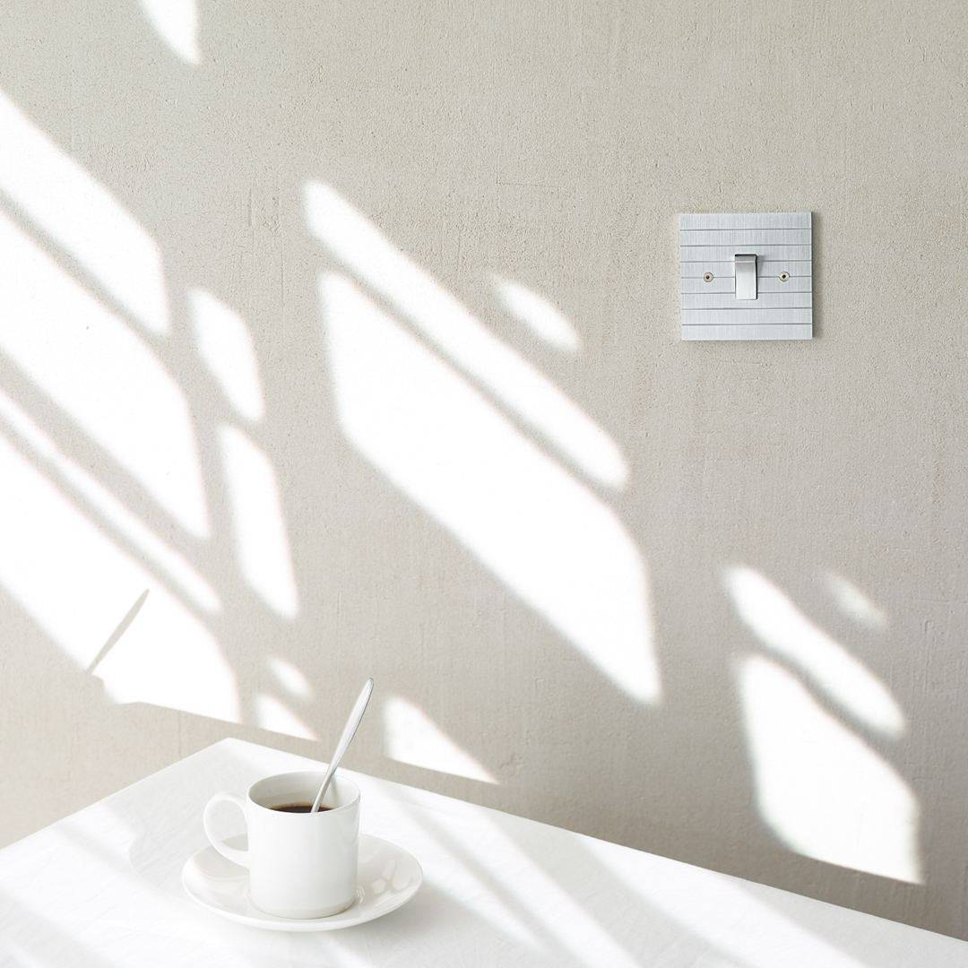 Designer light switches by Kelly Hoppen for Focus SB. A silver light switch on a grey wall above a white table with a cup of black coffee on it.
